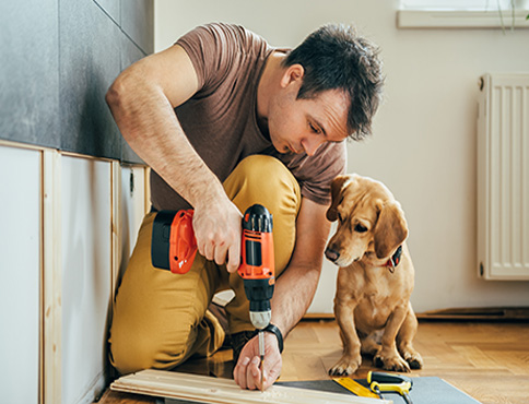 Man and his small dog doing some renovation work at home.